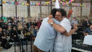 Arturo O'Farrill and Jorge Castillo hug after performing at the border wall in May 2018